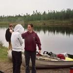 Spraying Bug Spray on Canoeing Trip
