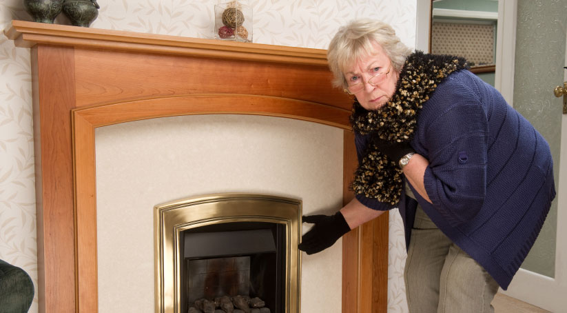 Woman turns on fireplace for warmth
